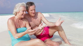 Senior Couple Sitting On Beautiful Beach. Senior couple sit at water's edge chatting together before man helps woman up and they walk out of frame.Shot on Canon stock footage