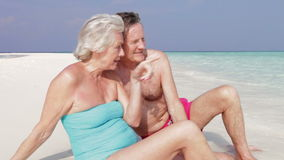 Senior Couple Sitting On Beautiful Beach. Senior couple sit at water's edge chatting together.Shot on Canon 5d Mk2 with a frame rate of 30fps stock video