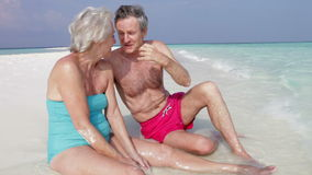 Senior Couple Sitting On Beautiful Beach. Senior couple sit at water's edge chatting together.Shot on Canon 5d Mk2 with a frame rate of 30fps stock video footage