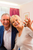 Senior couple sitting on bed in hotel room Royalty Free Stock Image