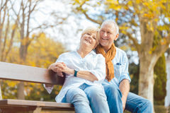 Senior couple sitting on bench in autumn park Royalty Free Stock Photos