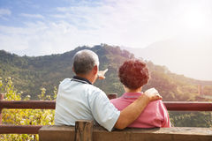 Senior couple sitting on the bench looking the nat. Senior couple are sitting on the bench looking the nature view in their happy time Royalty Free Stock Image
