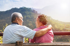 Senior couple sitting on the bench in nature park Stock Photo