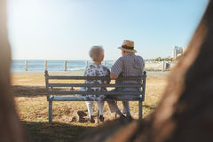 Senior couple sitting on a bench outdoors Stock Image