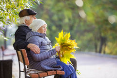 Senior couple sitting on bench in park Royalty Free Stock Photo