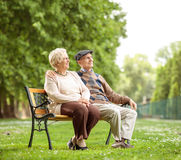 Senior couple sitting on a bench in the park Stock Images