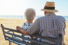 Senior couple sitting on a bench at the seaside Stock Photo