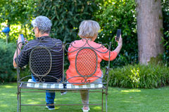 Senior couple sitting on bench with smartphones Royalty Free Stock Image