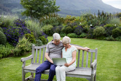 Senior couple sitting on bench and using laptop. In lawn Stock Image