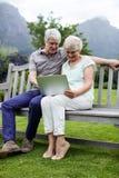 Senior couple sitting on bench and using laptop Stock Photos