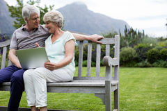 Senior couple sitting on bench and using laptop. In lawn Royalty Free Stock Photo