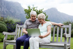 Senior couple sitting on bench and using laptop. In lawn Royalty Free Stock Photography