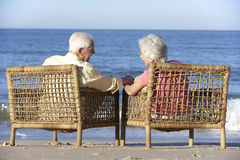Senior Couple Sitting In Chairs Relaxing On Beach Stock Image