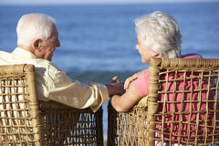 Senior Couple Sitting In Chairs Relaxing On Beach Royalty Free Stock Image