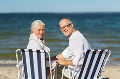 Senior couple sitting on chairs at summer beach Royalty Free Stock Photo