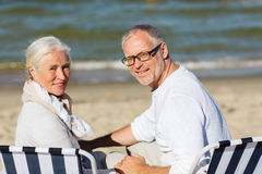 Senior couple sitting on chairs at summer beach. Family, age, travel, tourism and people concept - happy senior couple sitting on deck chairs on summer beach Stock Photography