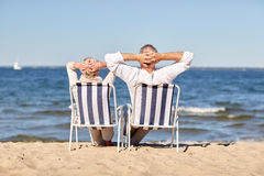 Senior couple sitting on chairs at summer beach. Family, age, travel, tourism and people concept - happy senior couple sitting on deck chairs on summer beach Royalty Free Stock Image