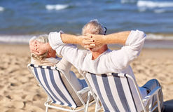 Senior couple sitting on chairs at summer beach. Family, age, travel, tourism and people concept - happy senior couple sitting on deck chairs on summer beach Royalty Free Stock Photography