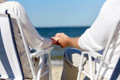 Senior couple sitting on chairs at summer beach. Family, old age, travel, tourism and people concept - close up of happy senior couple sitting on deck chairs on Royalty Free Stock Images