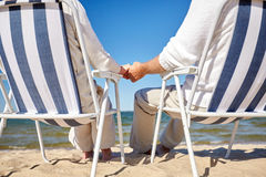 Senior couple sitting on chairs at summer beach. Family, old age, travel, tourism and people concept - close up of happy senior couple sitting on deck chairs on Royalty Free Stock Photography