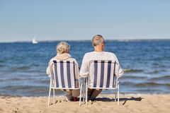 Senior couple sitting on chairs at summer beach. Family, old age, travel, tourism and people concept - happy senior couple sitting on deck chairs on summer beach Royalty Free Stock Photo