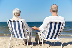 Senior couple sitting on chairs at summer beach. Family, old age, travel, tourism and people concept - happy senior couple sitting on deck chairs on summer beach Stock Image