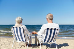 Senior couple sitting on chairs at summer beach. Family, old age, travel, tourism and people concept - happy senior couple sitting on deck chairs on summer beach Stock Photography