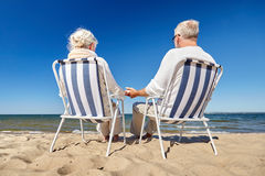 Senior couple sitting on chairs at summer beach. Family, old age, travel, tourism and people concept - happy senior couple sitting on deck chairs on summer beach Royalty Free Stock Image