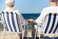 Senior couple sitting on chairs at summer beach. Old age, travel, tourism and people concept - close up of happy senior couple sitting on deck chairs on summer Royalty Free Stock Images
