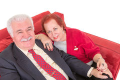 Senior couple sitting on a comfortable red couch Royalty Free Stock Photo