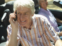 Senior couple sitting in convertible car, focus on man using mobile phone, smiling, side view Stock Photos