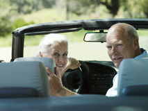 Senior couple sitting in convertible car, looking over shoulder, smiling, rear view, portrait Stock Photography