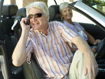 Senior couple sitting in convertible car, man in sunglasses using mobile phone, smiling, side view Stock Image