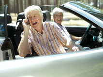 Senior couple sitting in convertible car, man using mobile phone, smiling, side view Stock Images