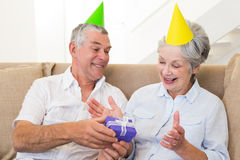 Senior couple sitting on couch celebrating a birthday Stock Photo