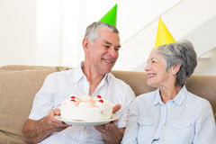 Senior couple sitting on couch celebrating a birthday Royalty Free Stock Photo