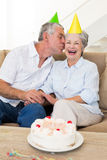 Senior couple sitting on couch celebrating a birthday Royalty Free Stock Images