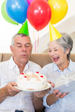 Senior couple sitting on couch celebrating a birthday Royalty Free Stock Photos