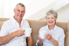 Senior couple sitting on couch drinking coffee smiling at camera Stock Photography