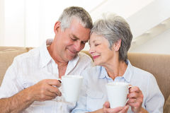 Senior couple sitting on couch drinking coffee touching heads Stock Images