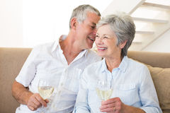Senior couple sitting on couch drinking white wine Royalty Free Stock Photo