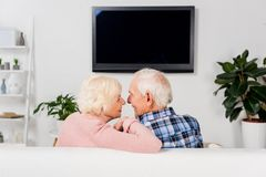 senior couple sitting on couch in front of tv royalty free stock photo