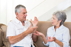 Senior couple sitting on couch having an argument Royalty Free Stock Photo
