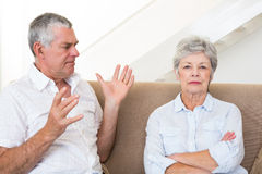 Senior couple sitting on couch having an argument Stock Image