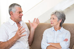 Senior couple sitting on couch having an argument Stock Photo