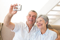 Senior couple sitting on couch taking a selfie Stock Photography