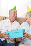 Senior couple sitting on couch wearing party hats holding a gift Royalty Free Stock Photo