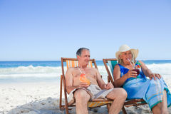 Senior couple sitting on deck chairs Stock Photography