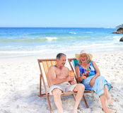 Senior couple sitting on deck chairs. Happy senior couple sitting on deck chairs Royalty Free Stock Image
