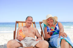 Senior couple sitting on deck chairs Royalty Free Stock Photos